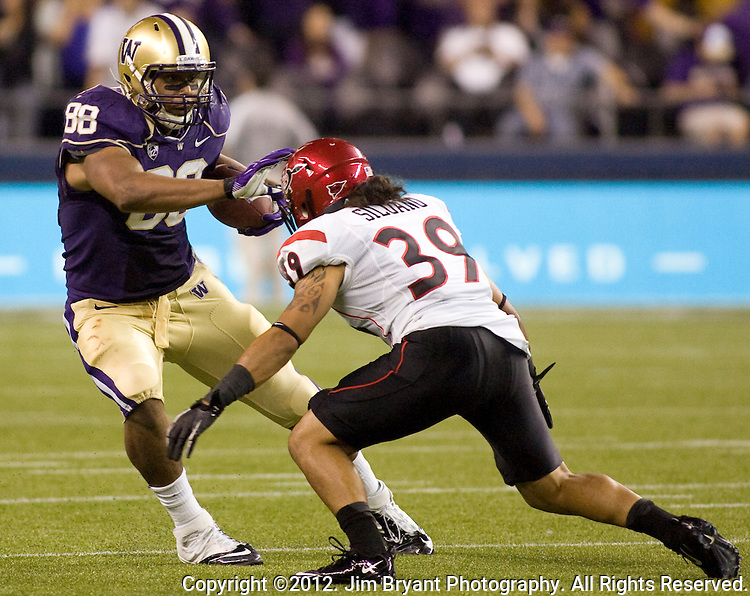 Washington's 'Austin Seferian-Jenkins  tries to stiff arm San Diego State linebacker Rene Siluano  in a college football game at CenturyLink Field in Seattle, Washington on September 1, 2012  The Huskies beat the Aztecs 21-12.  © 2012. Jim Bryant Photo. All Rights Reserved.