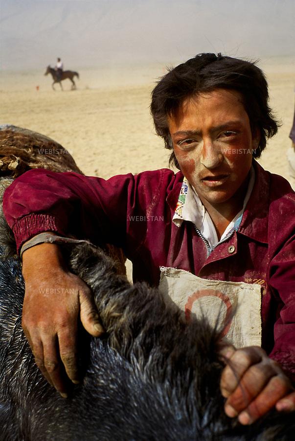 """1995. Portrait of a young Tajik rider, the face covered of sand, after a race in the plain of Mazar during the 40th anniversary of the """"independence"""" of Taxkorgan Tajik Autonomous County. Portrait d'un jeune cavalier tadjik, le visage couvert de sable, après une course de chevaux dans la plaine de Mazar lors du 40e anniversaire de """"l'indépendance"""" du comté autonome tadjik de Taxkorgan."""