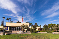 The main entrance to the lovely municipal auditorium at South Gate Park, showing the rose garden, flag, lighting, mature trees, and streaks of clouds in a blue sky.