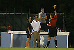 24 September 2009: Referee Ryan Cigich shows the yellow card to Duke head coach Robbie Church (in white), flanked by assistant coach Carla Overbeck. The University of North Carolina Tar Heels defeated the Duke University Blue Devils 2-1 in sudden victory overtime at Fetzer Field in Chapel Hill, North Carolina in an NCAA Division I Women's college soccer game.