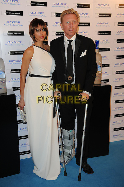 "Sharlely ""Lilly"" Kerssenberg & Boris Becker.Grey Goose Winter Ball to benefit the Elton John AIDS Foundationl at the Battersea Evolution, Battersea Park, London, England..29th October 2011.full length black suit white one shoulder dress crutches injury wound broken leg cast married husband wife .CAP/CAS.©Bob Cass/Capital Pictures."