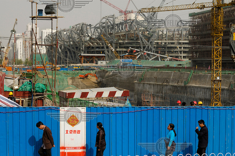 People passing the construction site of the 2008 Olympic stadium. The original 'bird's nest' design by architects Herzog & de Meuron was simplified by the Chinese once the bid for the Olympic games was successful.