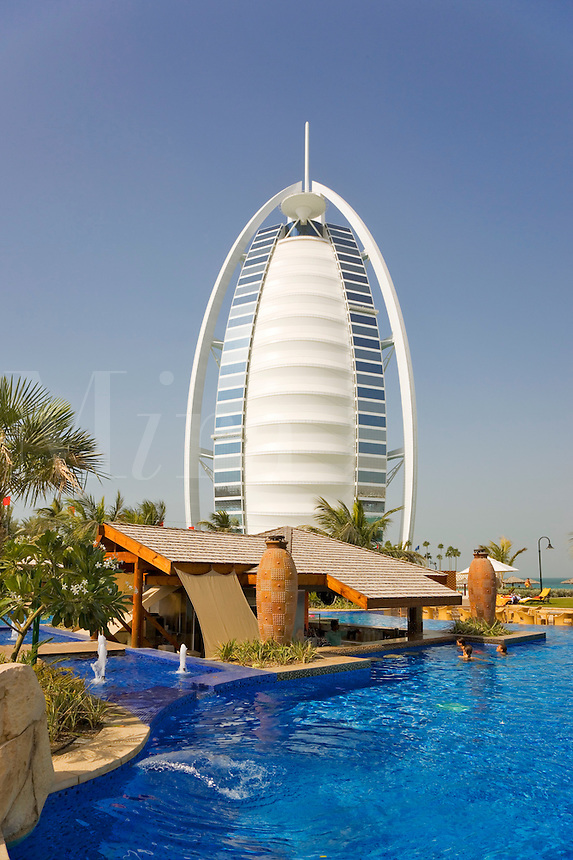 Dubai.  View of Burj al Arab Hotel over executive pool area, pavilions and gardens of Jumeirah Beach Hotel..