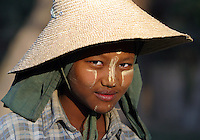 A Burmese girl is photographed near Bago, Myanmar (Burma).  The markings on her face are the Burmese version of suntan lotion made from a local plant.