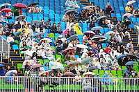 The specatators take cover as the rain comes down during the Grand Prix Special for the Equestrian Dressage. Rio 2016 Olympic Games, Centro Olímpico de Hipismo, Rio de Janeiro, Brazil. Friday 12 August. Copyright photo: Libby Law Photography