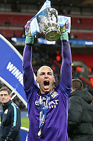 Wilfredo Caballero of Manchester City celebrates by holding the trophy aloft after winning the Capital One Cup by beating Liverpool on penalties at Wembley Stadium, London, England on 28 February 2016. Photo by David Horn / PRiME Media Images.