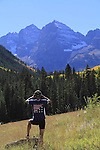 Caucasian male looking at the Maroon Bells with binoculars with autumn Aspen trees, west of the town of Aspen, Colorado, USA John offers fall foliage photo tours throughout Colorado.