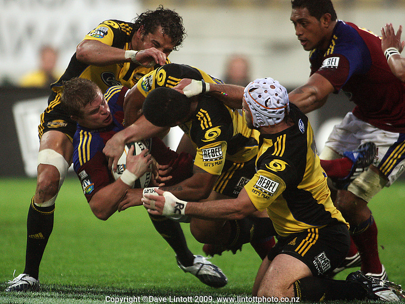 Jason Kawau, David Smith and Scott Waldrom combine to tackle Kendrick Lynn during the Super 14 rugby union match between the Hurricanes and Highlanders at Westpac Stadium, Wellington, New Zealand on Friday 20 February 2009. Photo: Dave Lintott / lintottphoto.co.nz