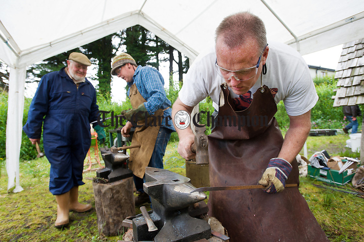 Blacksmith Eric O Neill at work on the anvil as part of the Iniscealtra Festival of Arts at Mountshannon with David Humphries and Steven Quinn behind. Photograph by John Kelly.