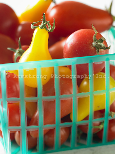 A plastic basket of red and yellow cherry tomatoes.
