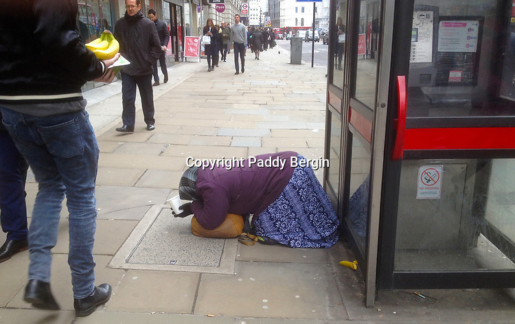 Woman begging in Moorgate, City of London while a man carrying bananas walks by.<br /> <br /> Stock Photo by Paddy Bergin