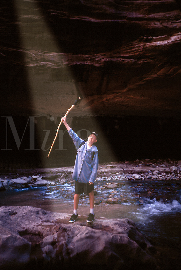 13 year old boy holding upraised walking stick in sunbeam. Utah United States The Narrows.