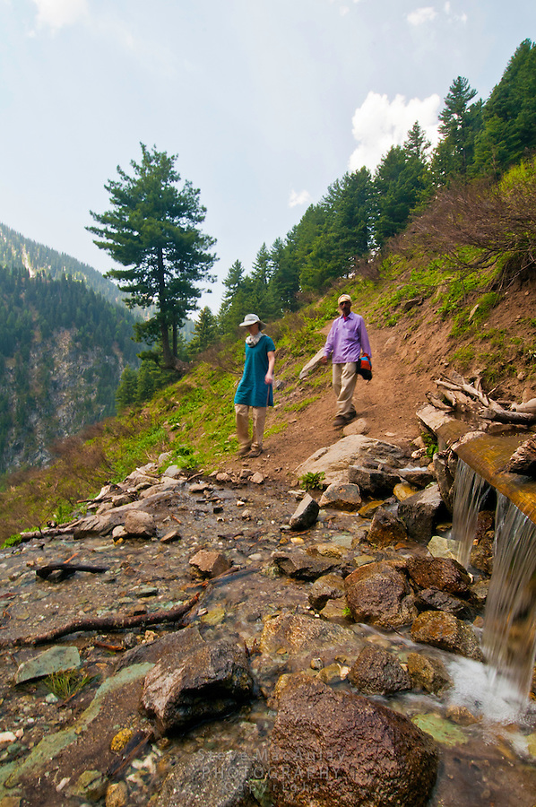 Wstern tourist and local guide approaching a small stream and waterfall, Gangabal Lake region of Kashmiri Himalayas, India.