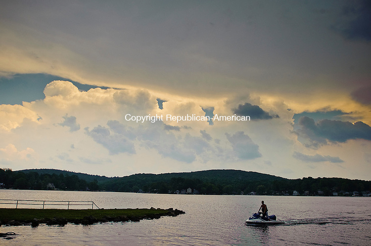 WINSTED, CT-18 JULY 2012--071812JS01- A person on a personal watercraft makes his way into the dock at Highland Lake as a thunderstorm rolls in to the Winsted area on Wednesday afternoon. .Jim Shannon Republican-American
