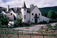 Exterior view of the Chateau Julien winery provides an example of classic French architecture. Grape vines grow along a trellis in the foreground. Carmel Valley, California.