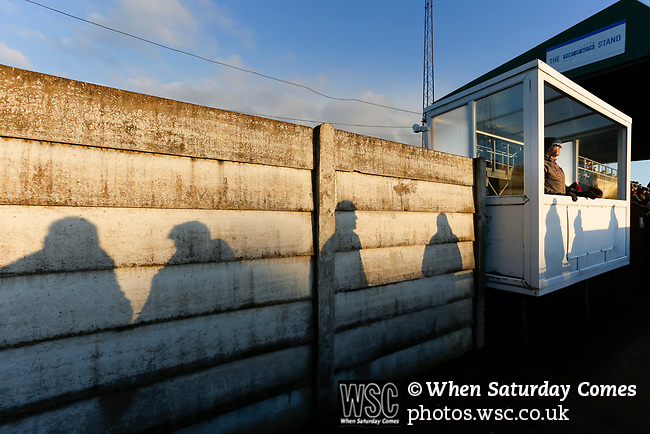 Fan's shadow cast on a wall by the low winter Sun. Blyth Spartans v Brackley Town, 30112019. Croft Park, National League North. Photo by Paul Thompson.
