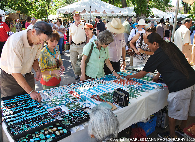 Visitors shop for colorful jewelery and other crafts on the plaza while visiting the Santa Fe Indian Market which is held each August in Santa Fe.