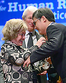 Annette Lantos, wife of the late United States Representative Tom Lantos (Democrat of California), left, awards Chen Guangcheng, the blind Chinese legal activist, right, the Tom Lantos Human Rights Prize in the United States Capitol on January 29, 2013.  Actor Richard Gere looks on from center..Credit: Ron Sachs