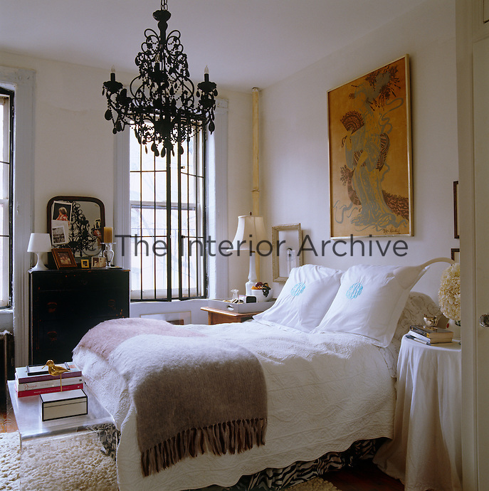 A black glass chandelier hangs above the bed