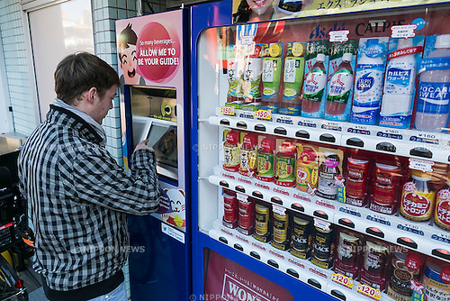 A Czech tourist receives information about Japanese beverages from an interactive vending machine in Asakusa district on January 22, 2016, Tokyo, Japan. Vending machines are popular across Japan but many sell drinks unknown to overseas visitors. As Japan tries to attract more tourists in the build up to the Tokyo Olympic Games in 2020, Asahi Group Holdings in collaboration with Nomura Research Institute set up its first interactive vending machine for English speakers near the Sensoji Temple in Asakusa. Customers can speak to the new machine which uses voice recognition technology to answer questions and to recommend Japanese drinks to foreign visitors. In 2015 the number of overseas visitors to Japan was 19.73 million, the highest number in 45 years. (Photo by Rodrigo Reyes Marin/AFLO)