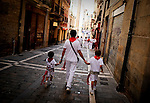A man with two children walking down a street in Pamplona during the San Fermin Festival, on July 12, 2012, in Pamplona, northern Spain. The festival is a symbol of Spanish culture that attracts thousands of tourists to watch the bull runs despite heavy condemnation from animal rights groups . (c) Pedro ARMESTRE