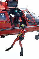 A swimmer is winched from the waters of San Francisco Bay by a United States Coast Guard HH-65C Dolphin helicopter. The helicopter and crew, based at U.S. Coast Guard Air Station San Francisco, was on a practice mission with the Coast Guard Auxilary to maintain search and rescue proficiency. Photographed 04/08