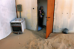 A woman with her baby at her caravan house, after strong winds that blew sands to her doorstep, at the Israeli outpost of Shirat Hayam, in the settlement bloc of Gush Katif, Gaza Strip. The young family has just moved in, arriving from the more bourgeois Gaza Strip Israeli settlement of Gadid. November 28, 2004.