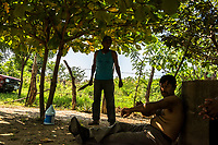 ARRIAGA, MEXICO - NOVEMBER 08: A local Mexican farmer (C) holding a kife, stands and talks to migrants prior to their eating lunch as they rest close to the home of the smuggler, Francisco Javier Martine on the 8th of November, 2015 in Arriaga, Mexico. <br /> <br /> Daniel Berehulak for The New York Times