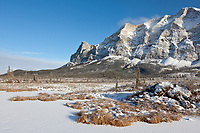 Frozen, snow covered winter tundra pond and the dramatic face of Mt Sukakpak of the Brooks Range mountains.