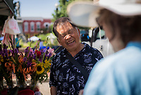 NWA Democrat-Gazette/CHARLIE KAIJO Xp Xiong of Siloam Springs laughs with a customer at his booth during the farmer's market, Saturday, July 7, 2018 at the Square in Bentonville. <br /><br />Area Farmers Markets are participating in a farmers market trail where patrons have passports that are stamped when they visit pariticipating markets. The event takes place through July and is an attempt to celebrate the diversity within the region&Otilde;s markets.