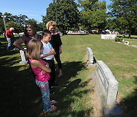 STAFF PHOTO ANDY SHUPE - Chris Terry, clockwise from left, her daughter Rebecca Redo, Redo's 10-year-old son, Collin, and 7-year-old daughter, Gracie, check out the restored grave markers during a dedication ceremony Sunday, Sept. 21, 2014, for the Gehring Cemetery at Christian Life Cathedral in Fayetteville.