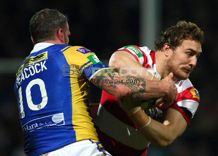 PICTURE BY VAUGHN RIDLEY/SWPIX.COM - Rugby League - Super League - Leeds Rhinos v Wigan Warriors - Headingley, Leeds, England - 15/03/13 - Wigan's Gil Dudson is tackled by Leeds Jamie Peacock.
