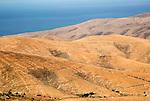 View of hills and sea in barren interior of Fuerteventura, Canary Islands, Spain