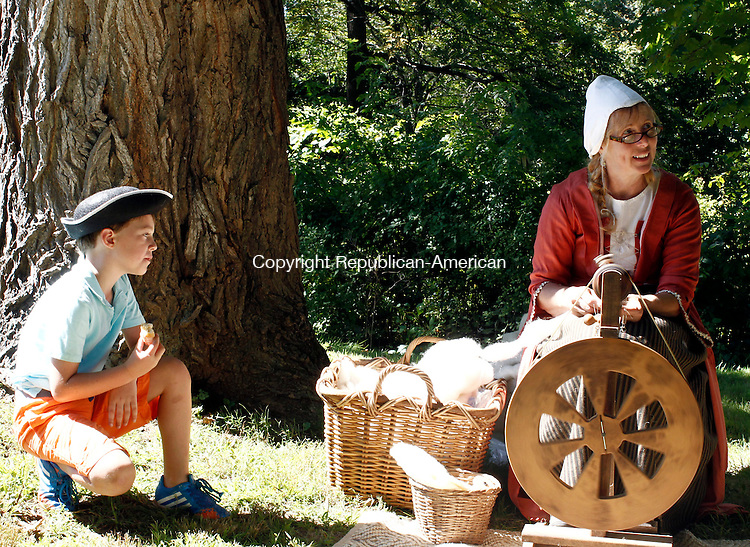 Tripp Clark, 7, left, of Woodbury watches as Diane Parmelee spins wool from a Shetland sheep, during the 20th annual Colonial Fair and Muster Day at the Hurd House in Woodbury on Sunday. The lawn of the historic home featured members of the Trumbull-Porter Chapter of the Daughters of the American Revolution, members of The Great Quinnehtukqut Company of Artificers and Traders portraying their work with tools and fabrics. The Gov. Oliver Wolcott Sr. Branch of the Sons of the American Revolution also performed and portrayed an encampment of civilians and soldiers.   Christopher Massa Republican-American