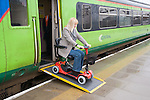Woman steering electric mobility scooter down access ramp to board a train. MR