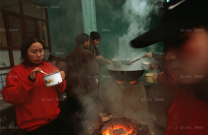 "Opera025 20030317 SHANXI, CHINA: A Jin Opera actress eats by a coal stove at the troupe's temporary residence in a small village in Shanxi Province, China 17 March 2003. With over 60 members to feed, usually noodles of some sort, are cooked in large pots that the Chinese endearly calls the ""iron rice bowl""."