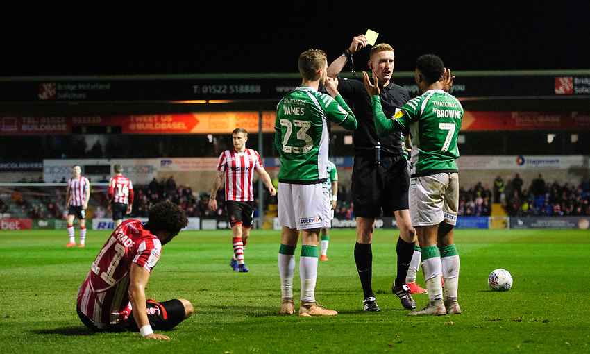 Yeovil Town's Rhys Browne is shown a yellow card by referee Scott Oldham<br /> <br /> Photographer Chris Vaughan/CameraSport<br /> <br /> The EFL Sky Bet League Two - Lincoln City v Yeovil Town - Friday 8th March 2019 - Sincil Bank - Lincoln<br /> <br /> World Copyright © 2019 CameraSport. All rights reserved. 43 Linden Ave. Countesthorpe. Leicester. England. LE8 5PG - Tel: +44 (0) 116 277 4147 - admin@camerasport.com - www.camerasport.com