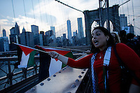 New York City, NY. 20 August 2014. A woman holds a Palestinian flag as she takes part during a Pro-palestine Rally across de Brooklyn Bridge in Manhattan.  Photo by Kena Betancur/VIEWpress