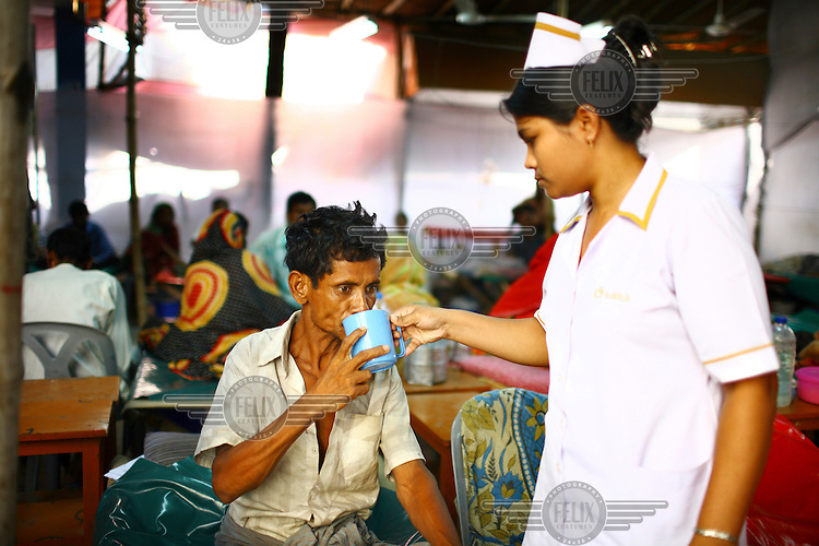 A nurse gives water to a man receiving treatment for diarrhoea at the International Centre for Diarrhoea Disease Research, Bangladesh (ICDDR B). The ICDDR is an international health research organization established in 1978 and credited with discovering oral dehydration therapy for the treatment of diarrhoea and cholera.