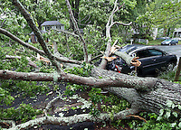 An Albemarle County firefighter is surrounded by branches from a fallen tree that crushed a vehicle and blocked a section of Idlewood Drive Saturday afternoon in Charlottesville, Va. Heavy winds downed several trees after storms moved thru the area. Photo/Andrew Shurtleff