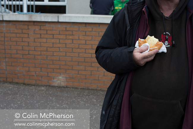 A spectator eating a pie at half-time as Edinburgh University took on Selkirk in a Scottish Lowland League match at Peffermill, Edinburgh in a game the hosts won 3-2. The match was one of six attended by members of GroundhopUK over the weekend to accommodate groundhoppers, fans who attempt to visit as many football venues as possible. Around 100 fans in two coaches from England participated in the 2016 Lowland League Groundhop and they were joined by other individuals from across the UK which helped boost crowds at the six featured matches.