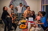 Carlos Saldaña is held back by his sister María Isabel Saldaña Grajales and Vicky;s grandson Adolfo, as Vicky Saldana and other family members look on during a birthday party for their grandson, Hector Yael, 10, (R) at a family gathering at Vicky's daughter, Cinthia Hernández Delgadilo's house in Xalapa, Mexico on November 4, 2017. <br /> Photo Daniel Berehulak for The New York Times