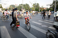 Cina, biciclette. Ragazzo in bicicletta attraversa le strisce pedonali <br />
