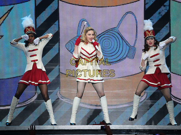 Madonna (Madonna Louise Ciccone) .Madonna performs at The Grand Garden Arena inside the MGM Grand Hotel and Casino, Las Vegas, Nevada, USA, .13th October 2012..music concert gig show live on stage performing full length red white cheerleader outfit costume knee high  boots baton collar gloves microphone singing .CAP/ADM/MJT.© MJT/AdMedia/Capital Pictures.