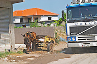 Street scene with horse drawn cart on the curb with a big Volvo truck lorry passing by on the road. Shkodra. Albania, Balkan, Europe.