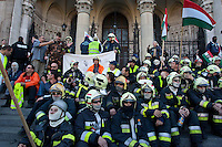Firemen and other law enforcement workers sit on the steps of the Hungarian Parliament during an anti-government rally to protest against the government's austerity measures in Budapest, Hungary on May 06, 2011..The government has launched a package of fiscal reforms to cut the budget deficit, including scrapping early retirement, which mostly affects law enforcement personnel. ATTILA VOLGYI