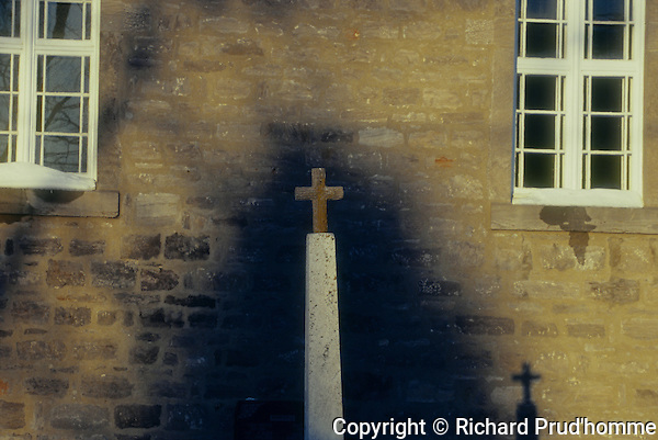 Old Catholic Church in Lavaltrie, Quebec, monument and shadow on Church wall. Shot on 35mm Fujichrome Astia 100F film.