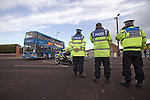 "Portsmouth 1 Southampton 1, 18/12/2012. Fratton Park, Championship. Police officers watcjing a convoy of buses containing Southampton fans approaching Fratton Park stadium down a closed-off street before Portsmouth take on local rivals Southampton in a Championship fixture. Around 3000 away fans were taken directly to the game in a fleet of buses in a police operation known as the ""coach bubble"" to avoid the possibility of disorder between rival fans. The match ended in a one-all draw watched by a near capacity crowd of 19,879. Photo by Colin McPherson."