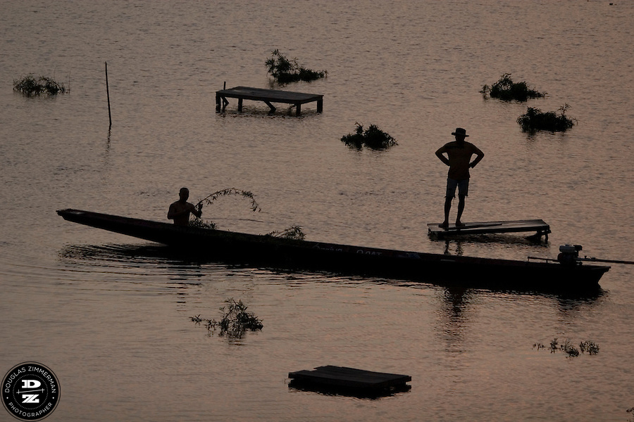 A fisherman moves in his boat in Mekong river in Vientiane, Laos just before sunset. Photograph by Douglas ZImmerman.