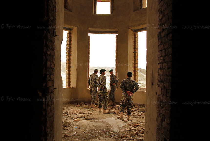 Members of the Afghan National Army walk around the rubble of the Darul Aman Palace on the outskirts of Kabul. ..The Palace was built in the early 1920s as a part of the endeavours by King Amanullah Khan to modernize Afghanistan. Intended as the seat for a future parliament outside of Kabul, the building was unused for many years after religious conservatives forced Amanullah from power and halted his reforms. It was first gutted by fire in 1969. It was restored to house the Defence Ministry during the 1970s and 1980s. During the Communist coup of 1978, the building was set on fire. It was damaged again as rival Mujahideen factions fought for control of Kabul during the early 1990s. Heavy shelling by the Mujahideen after the end of the Soviet invasion left the building a gutted ruin...